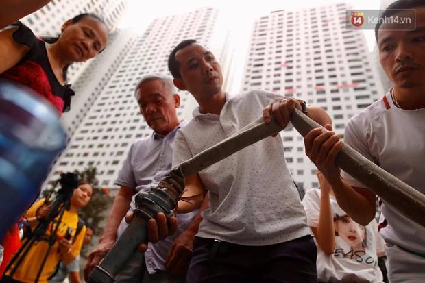 Ảnh, clip: Người dân chung cư HH Linh Đàm tiếp tục xếp hàng nhận nước sạch miễn phí, mòn mỏi chờ kết quả giám định nguồn nước có mùi lạ - Ảnh 13.