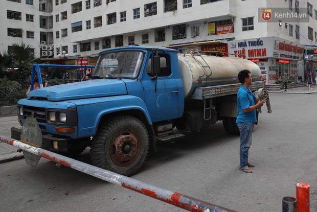 Ảnh, clip: Người dân chung cư HH Linh Đàm tiếp tục xếp hàng nhận nước sạch miễn phí, mòn mỏi chờ kết quả giám định nguồn nước có mùi lạ - Ảnh 4.