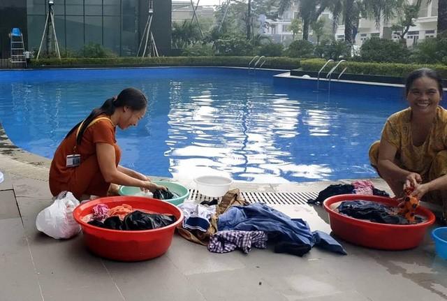 Cư dân mang quần áo giặt giũ, múc nước bể bơi để dùng trong cơn khát ở Hà Nội  - Ảnh 2.
