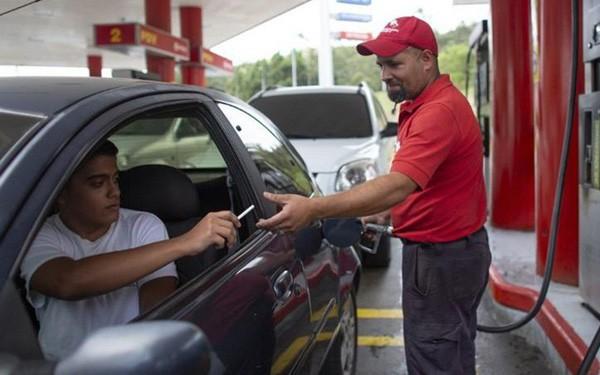 Tiền mất giá, người dân Venezuela dùng kẹo, thuốc lá...để mua xăng  - Ảnh 1.