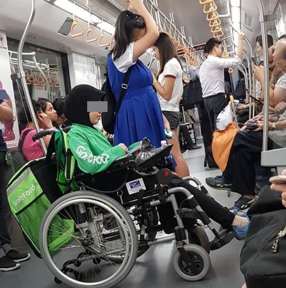 Hình ảnh gây sốt cộng đồng mạng của người phụ nữ ngồi xe lăn đi tàu điện ngầm để giao hàng cho GrabFood  - Ảnh 1.