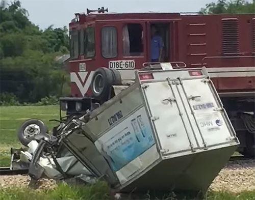 Xe tải bị tàu hỏa đâm bay 100 mét, tài xế đứt lìa chân - Ảnh 1.
