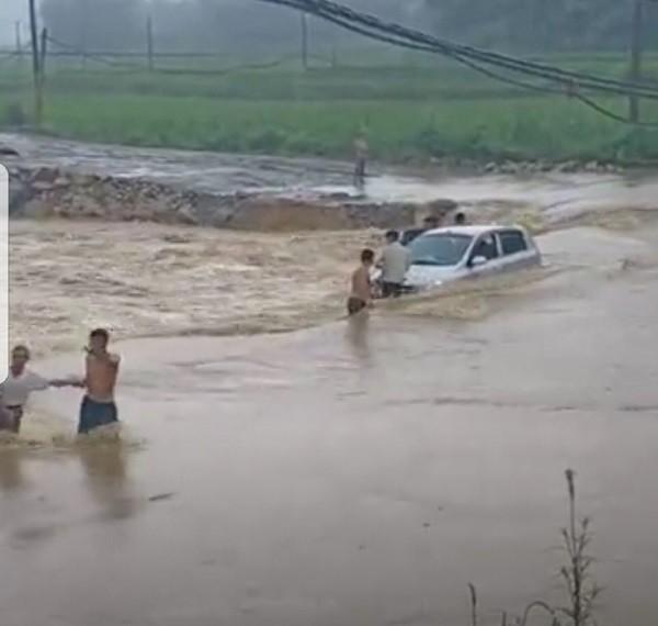 Cố đi qua đập tràn, ô tô bị lũ cuốn trôi, 4 người đạp cửa xe lao ra thoát thân - Ảnh 2.
