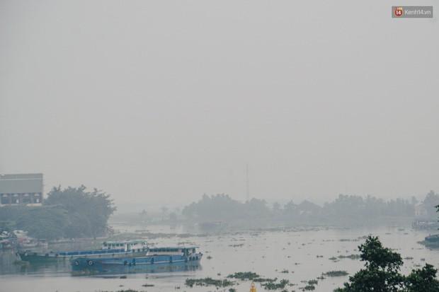 Ảnh: Sài Gòn bị bao phủ một màu trắng đục từ sáng đến trưa, người dân cay mắt khi đi ngoài trời - Ảnh 11.