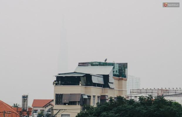 Ảnh: Sài Gòn bị bao phủ một màu trắng đục từ sáng đến trưa, người dân cay mắt khi đi ngoài trời - Ảnh 3.