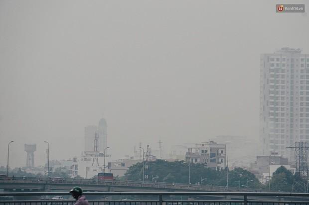 Ảnh: Sài Gòn bị bao phủ một màu trắng đục từ sáng đến trưa, người dân cay mắt khi đi ngoài trời - Ảnh 9.