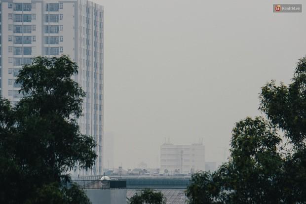 Ảnh: Sài Gòn bị bao phủ một màu trắng đục từ sáng đến trưa, người dân cay mắt khi đi ngoài trời - Ảnh 10.