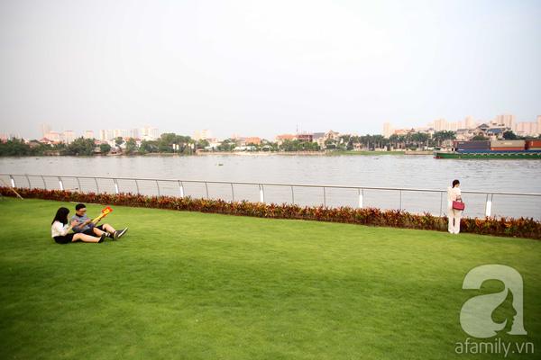 Đôi tình nhân ngồi hóng gió trên thảm cỏ xanh ngắt ở sát bở sông Sài Gòn.