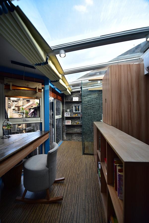 Tầng trên cùng của ngôi nhà được xử lý bằng mái kính có thể kéo rèm để chắn nắng. Đây cũng là không gian làm việc, thư giãn cho gia đình.