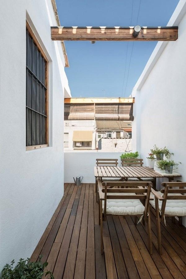 Góc ban công giản dị với sàn gỗ và nội thất gỗ.