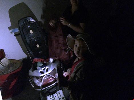 Việc cắt điện đã được báo trước cho người dân. Trong ảnh: Cháu bé đang cầm điện thoại có đèn để giúp mẹ cất đồ tại tầng hầm để xe chung cư