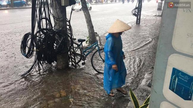 Một người dân phải dừng tạm bên đường do mưa quá lớn không di chuyển được. Ảnh: Định Nguyễn