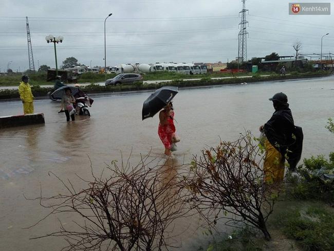 Tuyên đường tại khu vực Dương Nội (Hà Đông) chìm trong biển nước, người dân phải dắt xe và lội bộ qua đường. Ảnh: Lê Bảo