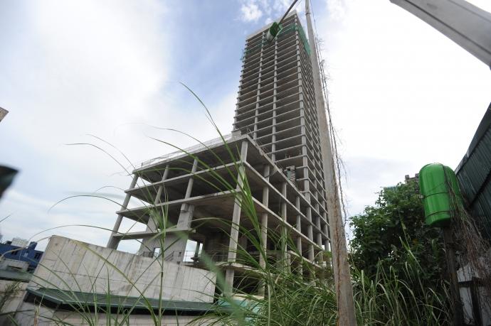 Trung tâm điều hành và Giao dịch Xi măng Việt Nam (Vicem Tower) mới hoàn thiện phần thô đã cho ngừng xây dựng khiến bên trong cỏ mọc um tùm.