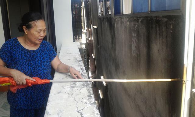 Bà Phạm Thị Sen, chủ nhà 161, sau một ngày mưa lại đem cán cờ đo khoảng cách giữa nhà nghiêng và nhà bà. Ảnh: H.Phương