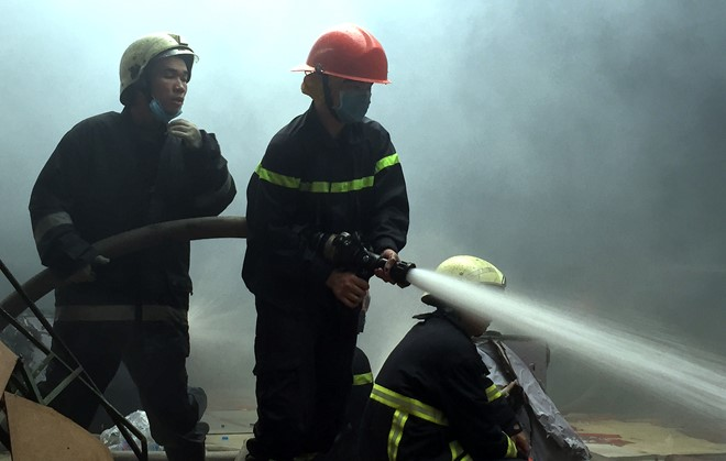 Lực lượng chức năng phun nước khống chế đám cháy. Ảnh: Lê Trai