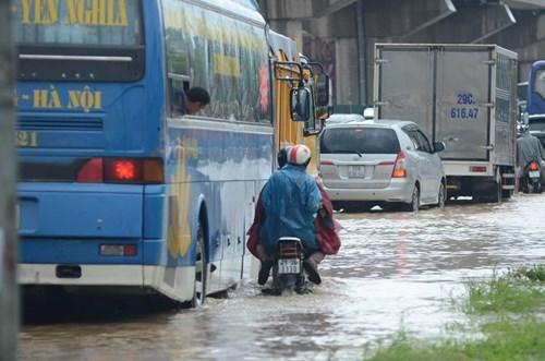 Mưa lớn khiến đường ngập sâu khoảng 30-50cm, các loại xe lưu thông gặp khó khăn. Lực lượng CSGT có mặt phân làn giao thông.