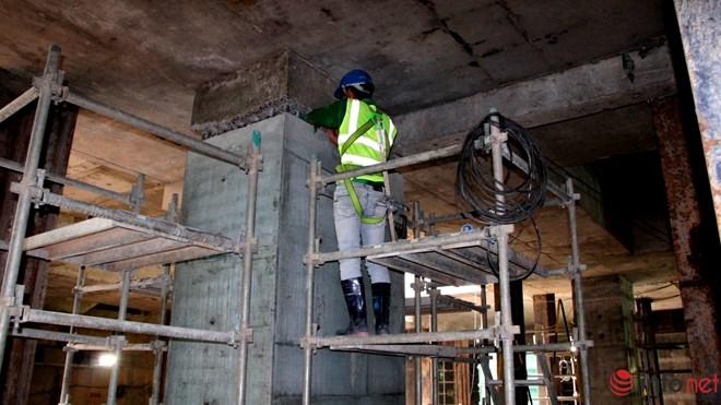 Một công nhân đang kiểm tra lại cọc bê tông mới đổ.