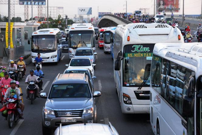 Ô tô khách, xe máy ùn ứ kéo dài khu vực cầu vượt Nguyễn Văn Linh - Ảnh: HỮU KHOA