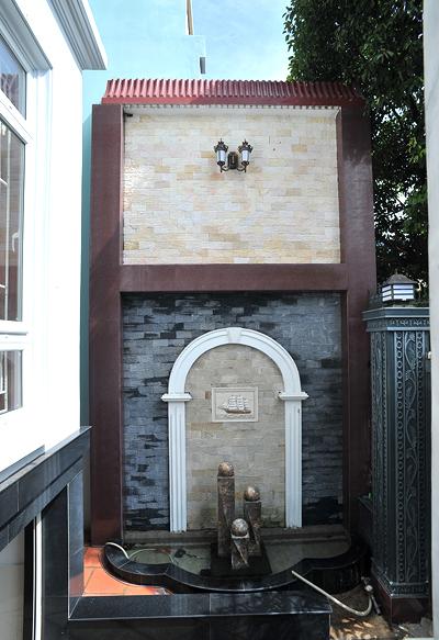 Một đài phun nước nhỏ được bố trí ngay cạnh cổng vào nhà.