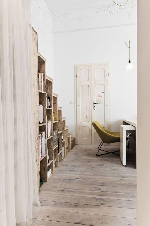 Phía sau ghế sofa là góc làm việc nhỏ với chiếc bàn trắng và chiếc đèn bàn cùng tông màu. Toàn bộ sàn nhà đều được ốp gỗ tạo nên một không gian vô cùng ấm cúng và sang trọng.