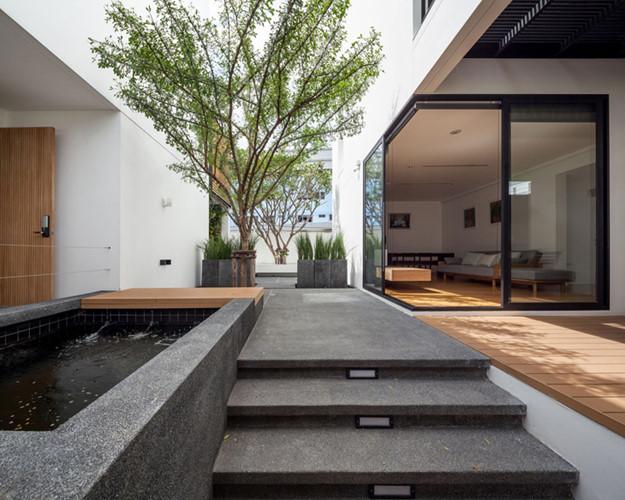 Khoảng sân chung nơi tầng 1 được chủ nhà trồng rất nhiều cây xanh và còn có cả hồ nước giúp điều hòa không khí cho hai ngôi nhà.