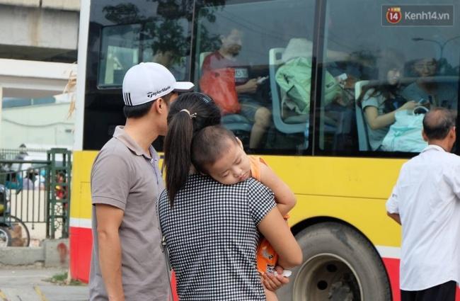 Nhiều trẻ em tỏ ra mệt mỏi sau khi xuống xe, ngủ ngặt nghẽo trên vai bố mẹ. Ảnh: Định Nguyễn