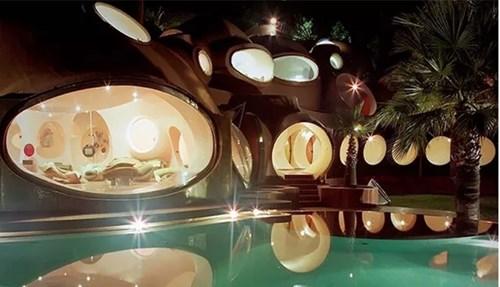 Vào ban đêm, ánh sáng từ bên trong căn nhà chiếu xuống hồ bơi tạo nên một không gian lung linh, tuyệt đẹp như một cung điện. Dinh thự này từngthuộc quyền sở hữu của nhà thiết kế thời trang nổi tiếng Pierre Cardin.
