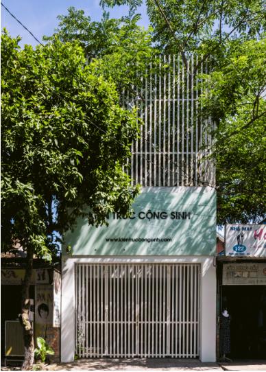 """Không """"kín cổng cao tường"""" như những ngôi nhà bình thường khác dọc khu phố, văn phòng Kiến trúc Cộng sinh thu hút mọi ánh nhìn của người qua đường bởi cửa cổng cũng như hàng rào bảo vệ bên trên là những thanh sắt thưa giúp cây cối phát triển tự nhiên và còn tạo không gian thông thoáng khi nhìn từ bên trong."""