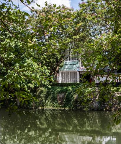 Văn phòng Kiến trúc Cộng sinh với cánh cửa sắt màu trắng nằm bên một dòng sông nhỏ của thành phố Huế.