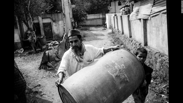 Một người đàn ông mang thùng ra đựng nước khi chiếc xe bồn mang nước đến Latur, Ấn Độ.