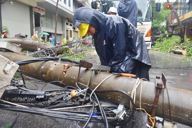 Trên đường Tuệ Tĩnh, lực lượng chức năng cũng đang tiến hành dọn dẹp, di dời chiếc cột điện bị đổ. Ảnh: Phương Thảo
