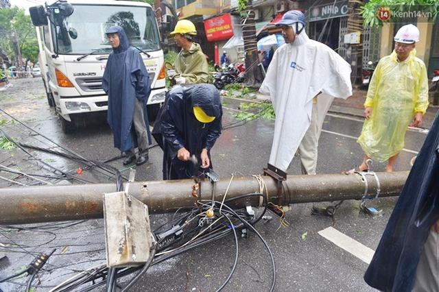 Chiếc cột điện đổ nằm chắn ngang đường gây ảnh hưởng không nhỏ đến giao thông đi lại. Ảnh: Phương Thảo