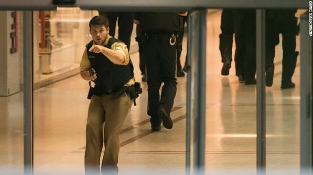 Một nhân viên cảnh sát bên trong khu trung tâm thương mại Olympia, nơi xảy ra vụ xả súng - Ảnh: AP.