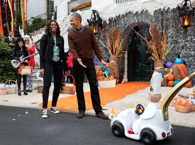 Tổng thống Mỹ Obama và Đệ nhất phu nhân thích thú trước cậu bé trong trang phục Đức Thánh Cha ngồi trên chiếc xe tí hon trong một sự kiện Halloween, trên bãi cỏ phía Nam của Nhà Trắng vào ngày 30 Tháng 10 năm 2015.