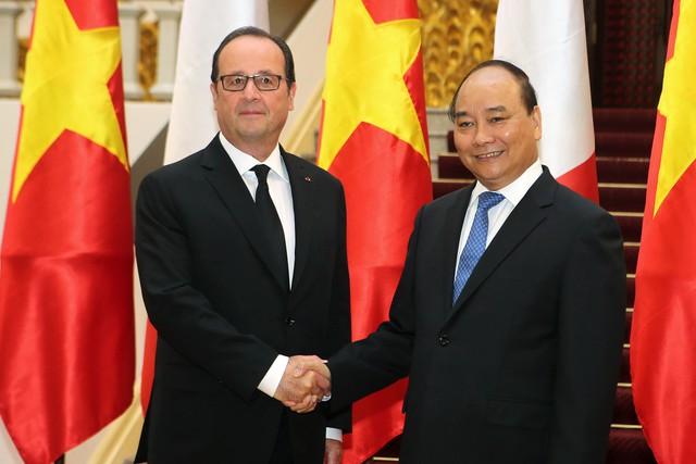 Thủ tướng Nguyễn Xuân Phúc (phải) bắt tay Tổng thống Hollande trong chuyến công du Việt Nam. Ảnh: Reuters
