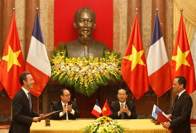 CEO Jetstar Pacific Lê Hồng Hà (phải) và CEO của Airbus (trái) ký hợp đồng mua bán máy bay A320 trước sự chứng kiến của Tông thống Hollande và Chủ tịch Trần Đại Quang (giữa). Ảnh: Reuters
