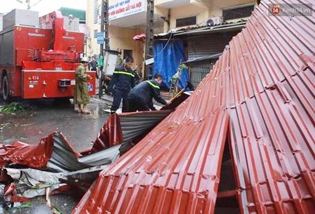 Những mái tôn rơi xuống đường đang được dọn dẹp. Ảnh: Phương Thảo