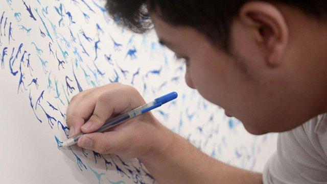 Chàng trai tự kỷ See Toh Sheng Jie vẽ hình khủng long - Ảnh: STRAITS TIMES