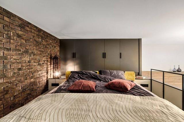 Không gian nghỉ ngơi trên gác được chủ nhà rất chau chuốt với hệ tủ sát trần và bức tường gạch thô cá tính.