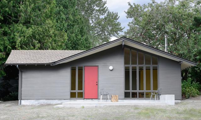 Mặt trước của căn nhà với cửa ra vào được sơn màu đỏ và những cửa kính được thiết kế nhiều ngăn cao sát trần.