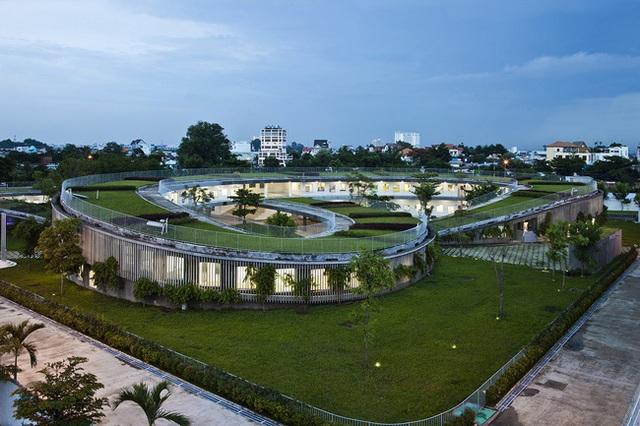 Ngôi trường mầm non được thiết kế hình xuyến kết nối mái nhà với sân chơi tạo nên một màu xanh trải dài.