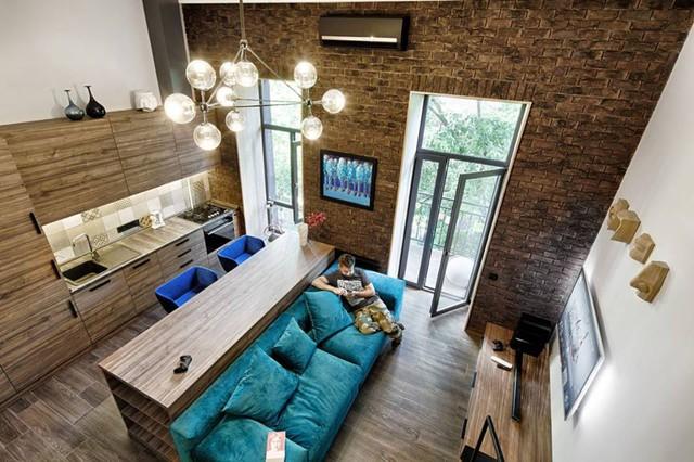 Không gian trong nhà lúc nào cũng tràn ngập ánh sáng với hai cửa kính lớn đầu hồi. Nội thất trong căn hộ hầu hết được làm từ gỗ với tông màu trầm vừa tạo cảm giác thân thiện nhưng không kém phần sang trọng.