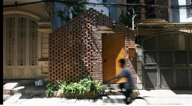 Ngôi nhà nhỏ nổi bật giữa khu phố bởi bức tường gạch thô xây xen kẽ trước nhà.