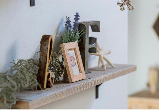 Bức ảnh thành viên trong gia đình cùng những đồ trang trí được đặt ngay ngắn trên kệ gỗ.