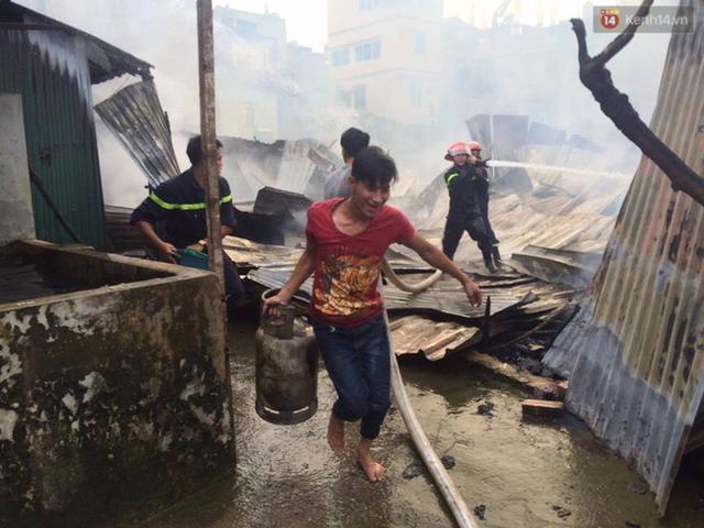 Nam thanh niên hỗ trợ đưa bình ga ra khỏi đám cháy