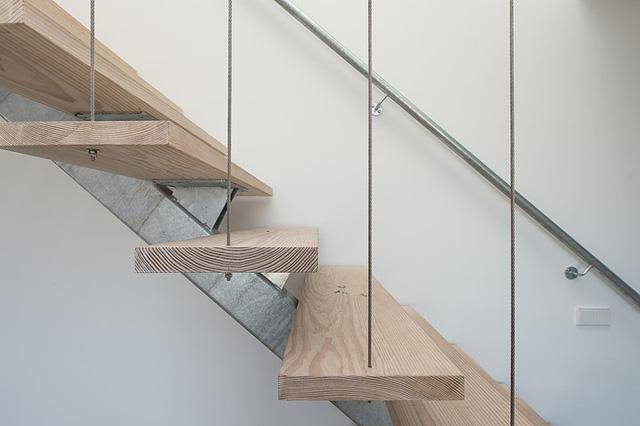 Cầu thang gỗ lên tầng được thiết kế đơn giản với tay vịn inox khiến không gian trở nên thoáng rộng hơn.