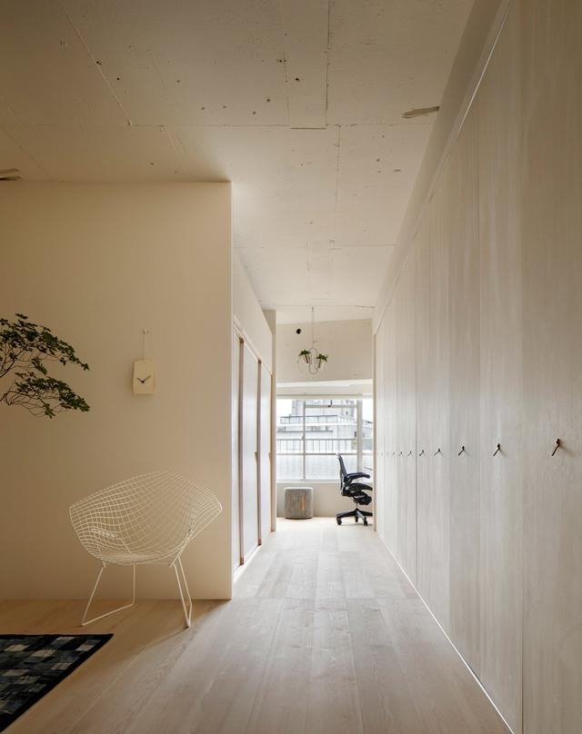 Với việc lựa chọn cùng một tông màu sáng từ màu sơn đến màu gỗ ốp sàn và hệ thống tủ gỗ chạy dài dọc bức tường của ngôi nhà khiến cho căn hộ nhỏ trở nên rộng và thoáng hơn. Khu vực nghỉ ngơi và phòng tắm được sử dụng cửa trượt truyền thống để tiết kiệm diện tích.