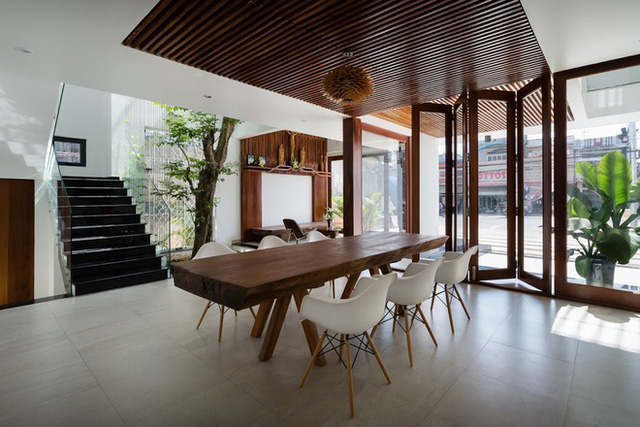 Chéo góc bên kia là phòng ăn lớn với chiếc bàn từ một thân gỗ xẻ to rộng, bao quanh là những chiếc ghế nhỏ màu trăng cách điệu.