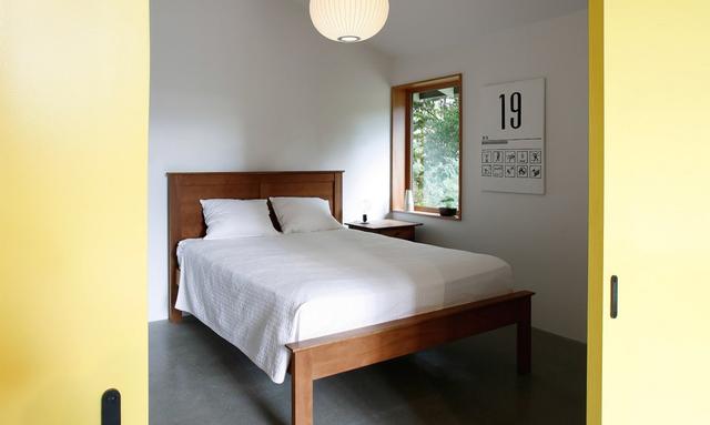 Cánh cửa trượt màu vàng chạy dọc chiều dài của ngôi nhà giúp gia chủ che đi không gian nghỉ ngơi riêng tư khi cần thiết.